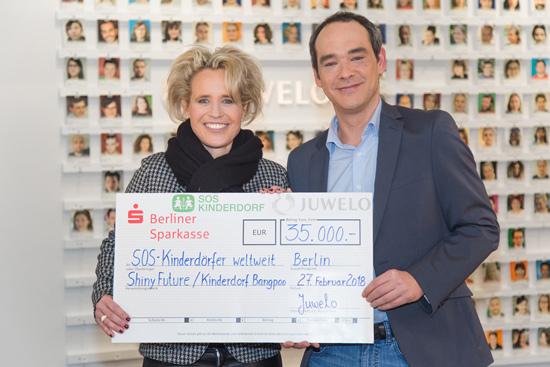 Feierliche Übergabe des Spendenschecks durch Juwelo-Mitbegründer Thomas Jarmuske an Sabine Fuchs von den SOS-Kinderdörfer international